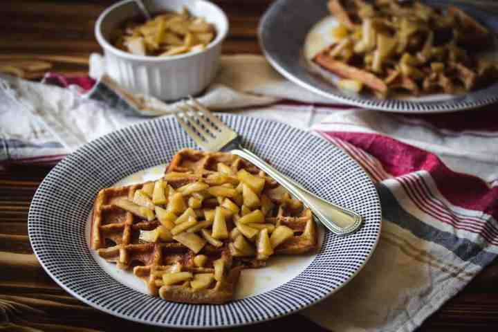two plates of gluten free applesauce waffles with apple topping