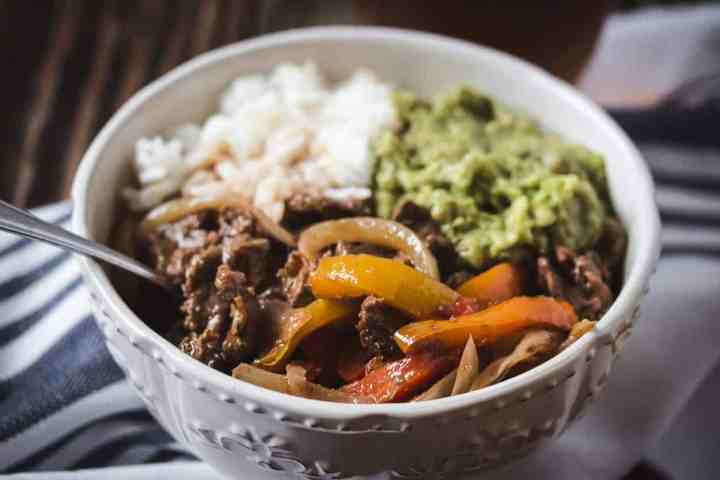 a bowl of gluten and dairy free air fryer fajitas with rice and guacamole