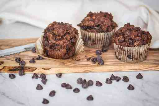 three gluten free chocolate zucchini muffins on a cutting board