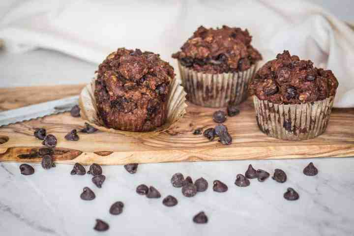 gluten free chocolate zucchini muffins on cutting board with chocolate chips around them