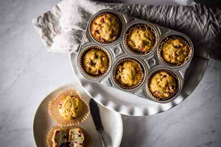 gluten free cranberry orange muffins in a tine and on a plate