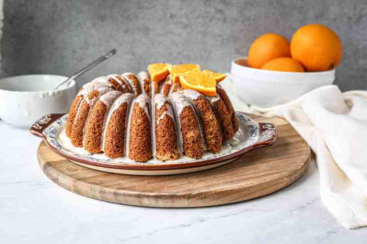 gluten free orange bundt cake on a platter with orange wedges