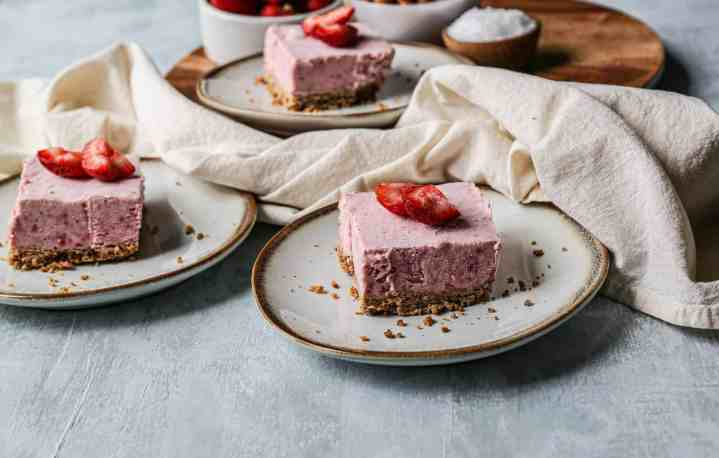 Three gluten free strawberry icebox bars on plates with fresh strawberries on top