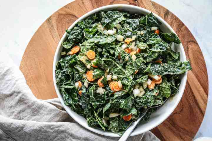 a large bowl of gluten free kale salad with peanut dressing