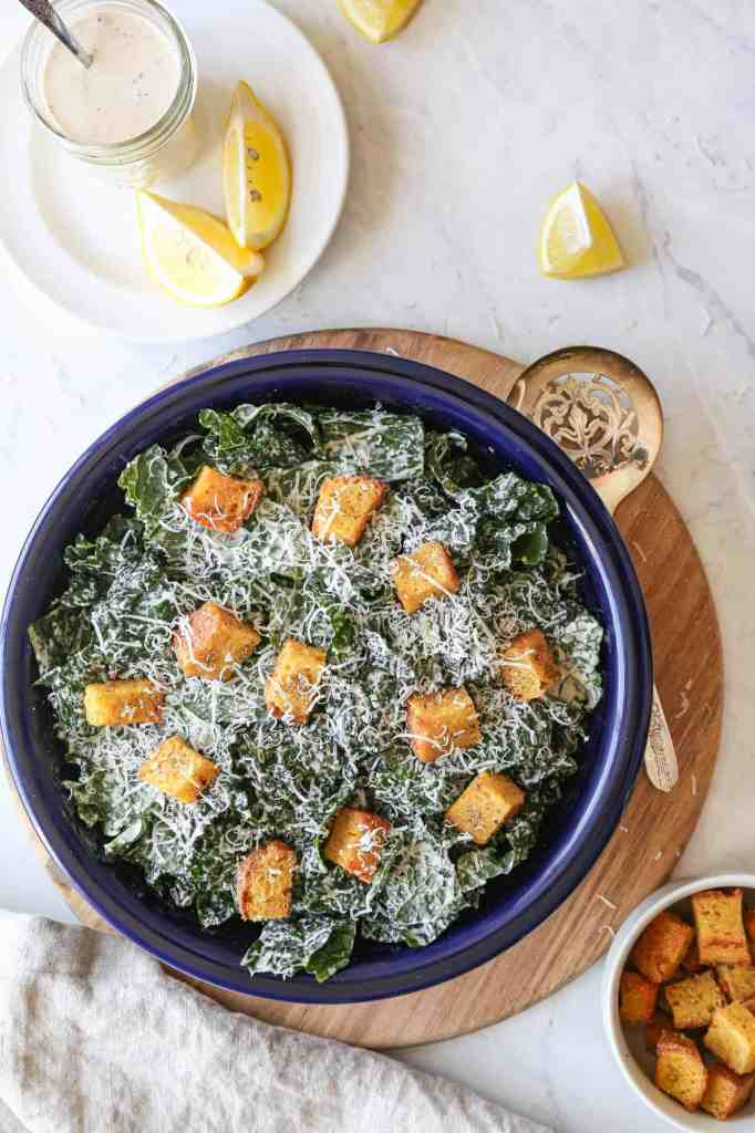 a large bowl of gluten free kale caesar salad with croutons and parmesan cheese