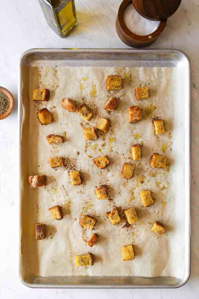 a baking sheet with gluten free sourdough croutons straight out of the oven