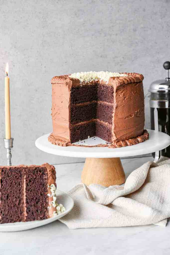 a gluten free chocolate mayonnaise cake on a cake stand with a slice of cake on a plate and a pot of coffee