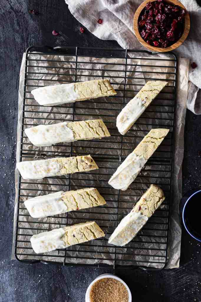 a cooling rack of gluten free orange cranberry biscotti dipped in white chocolate