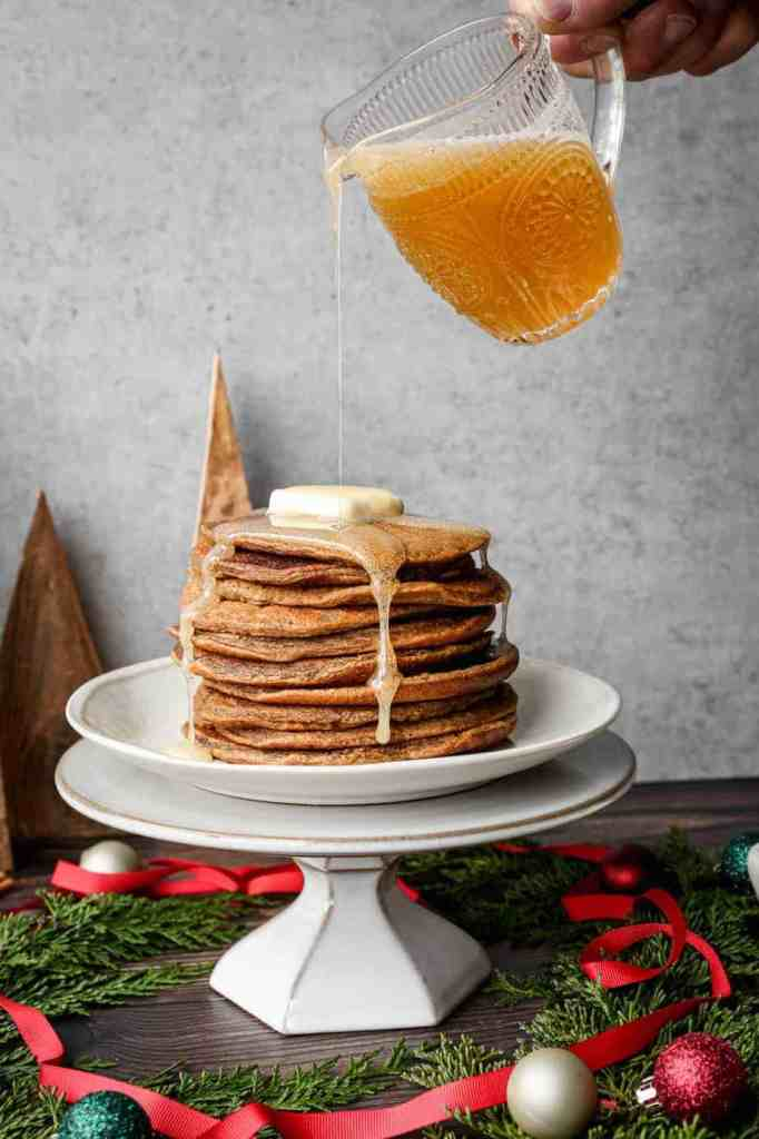 a stack of gluten free gingerbread pancakes with ginger syrup being poured over them