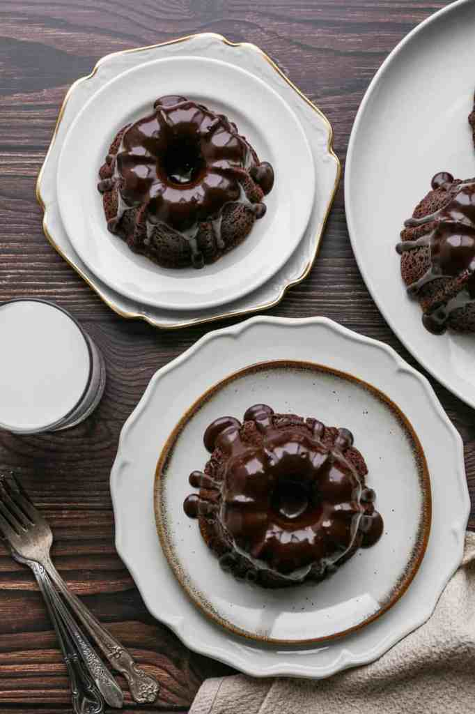 two mini gluten free double chocolate bundt cakes on white plates with glossy chocolate glaze over them