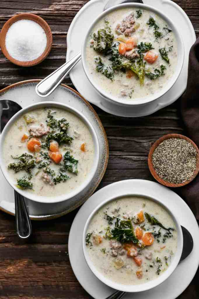three white bowls of gluten free instant pot sausage and kale soup
