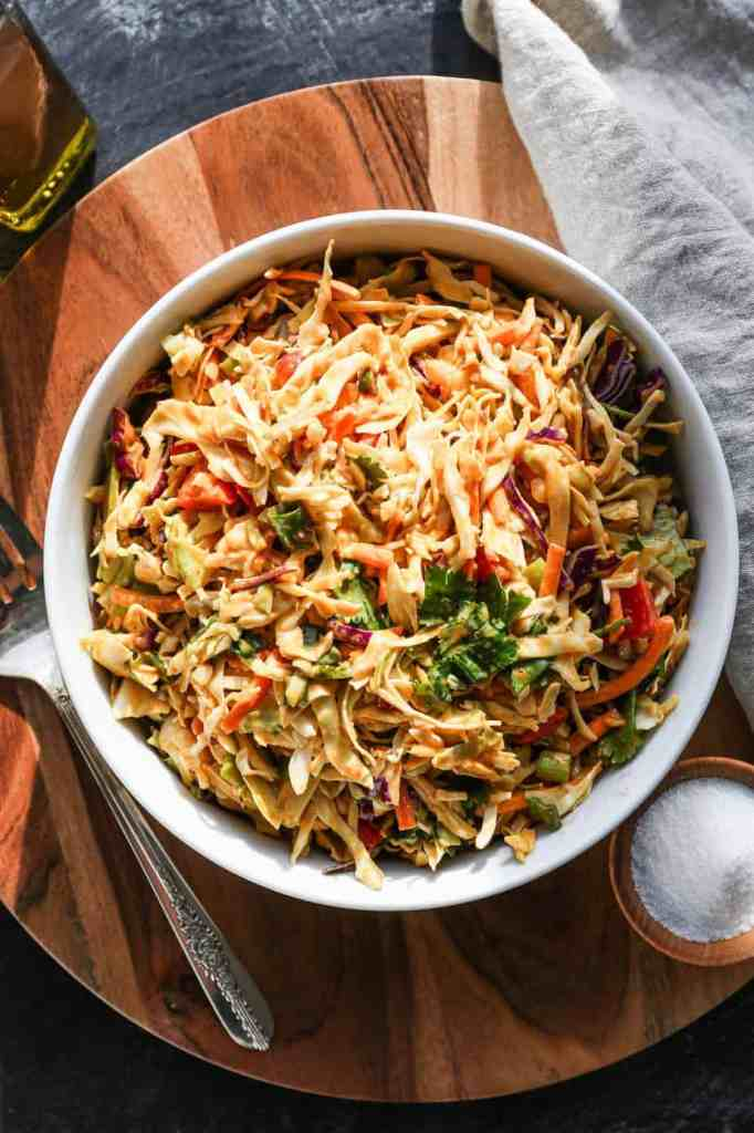 a white bowl of thai style cabbage salad