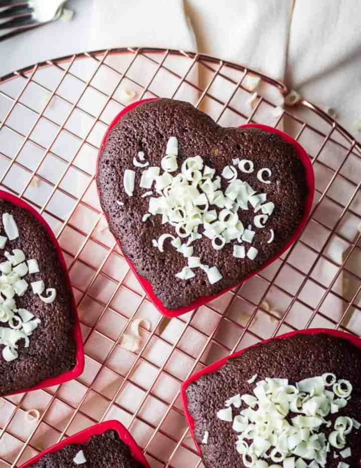 gluten free almond cocoa cakes baked in red heart shaped mini cake pans and topped with white chocolate curls