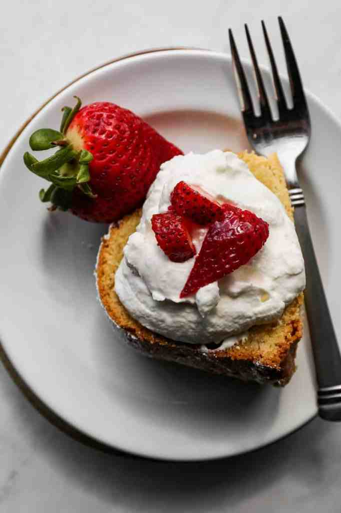 a slice of gluten free cream cheese pound cake on a white plate with sliced strawberries and homemade whipped cream on top