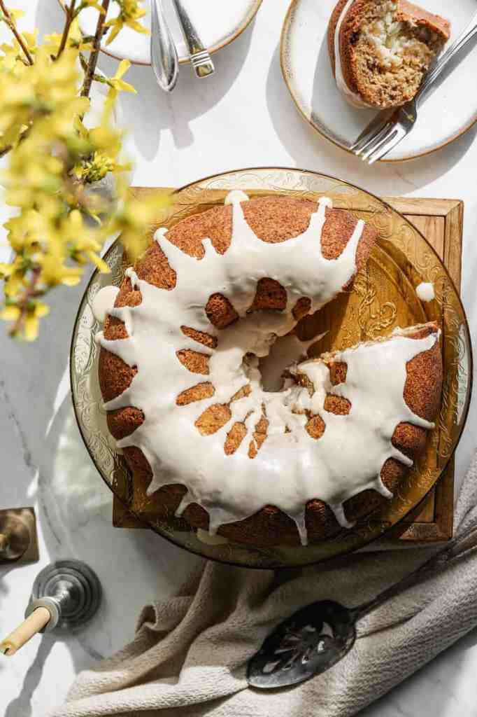a gluten free hummingbird bundt cake on a antique yellow platter with yellow forsythia blooms next to the cake