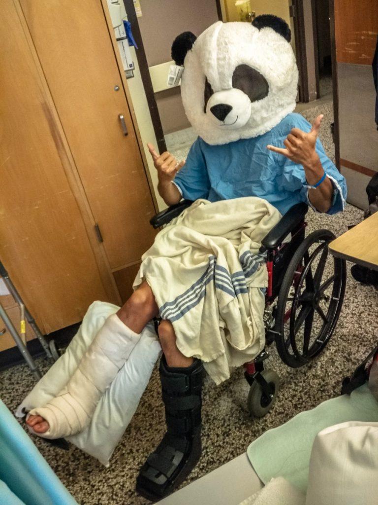 ragazzo con entrambe le gambe rotte indossa una testa di panda