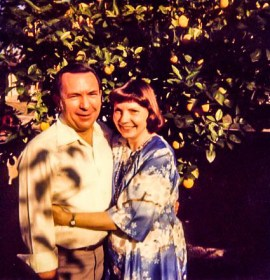 Jeanne and Don posing in the Lakewood back yard after opening presents, 1980s