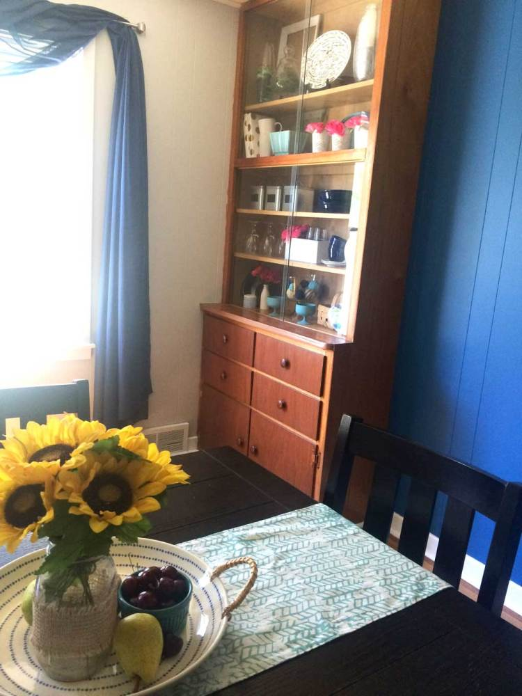 Pretty blue dining room with sunflower centerpiece and built-in hutch. Love the decor.