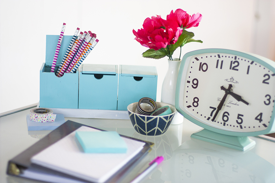 clock-and-office-supplies-on-desk