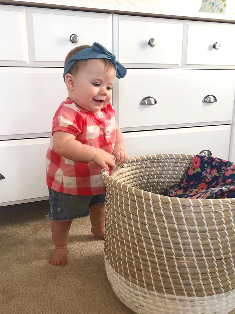 baby-standing-by-basket-in-nursery