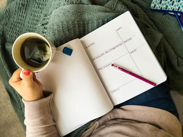 journal-notebook-on-lap-holding-tea