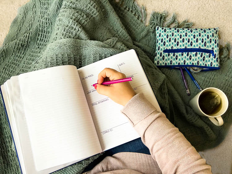 woman-holding-journal-on-lap