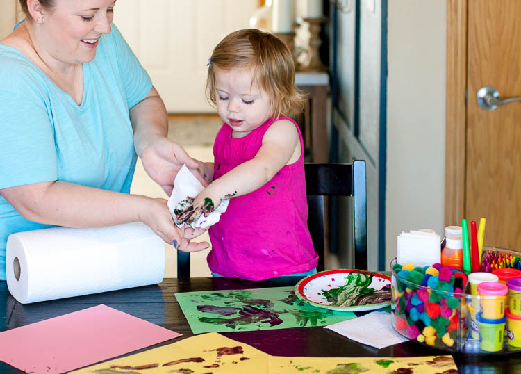 mom-wiping-finger-paint-off-toddlers-hands