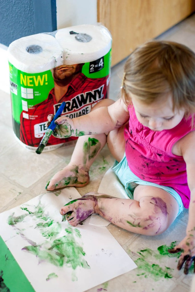 toddler painting foot on floor