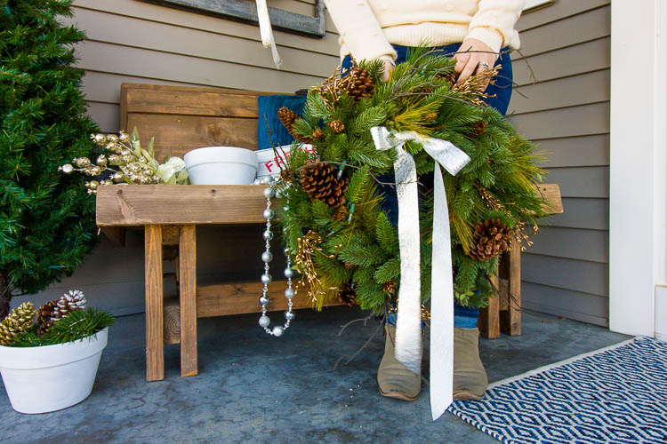 woman-holding-wreath-on-front-porch-at-christmas