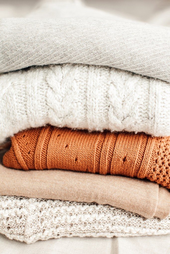 stack-of-sweaters-on-bed