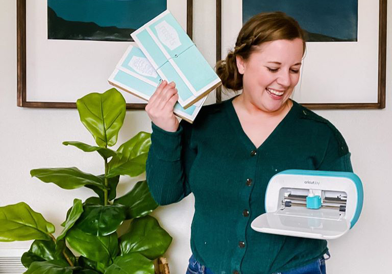 emily counts holding Cricut Joy and labeled accordion files