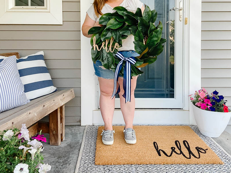 woman holding magnolia wreath on front porch with coir welcome mat painted