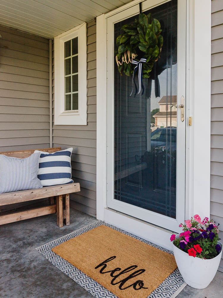 front porch with wreath on door and welcome mat