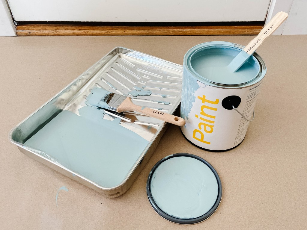 open can of paint with brush pan ready to paint