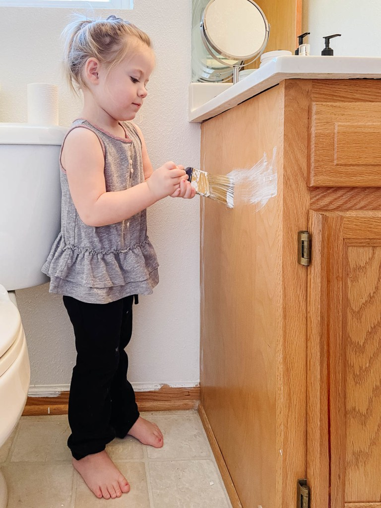 toddler painting a bathroom cabinet
