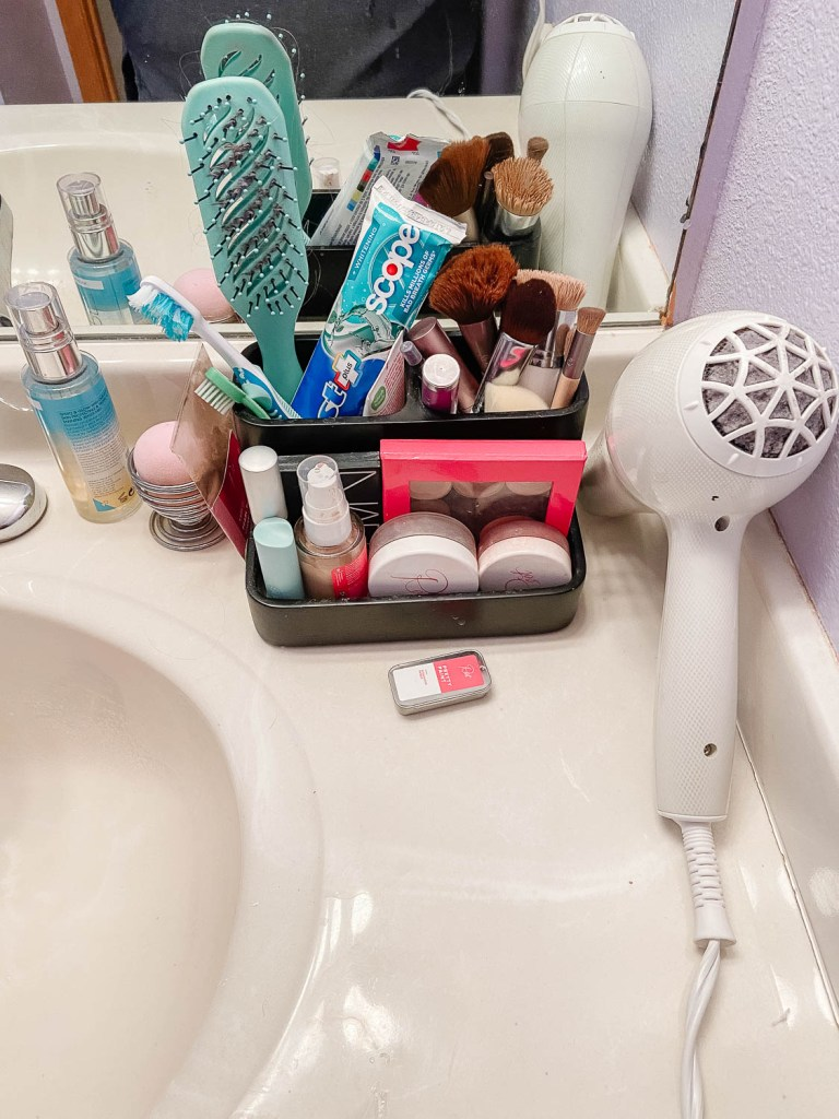 bathroom counter with makeup and hair supplies
