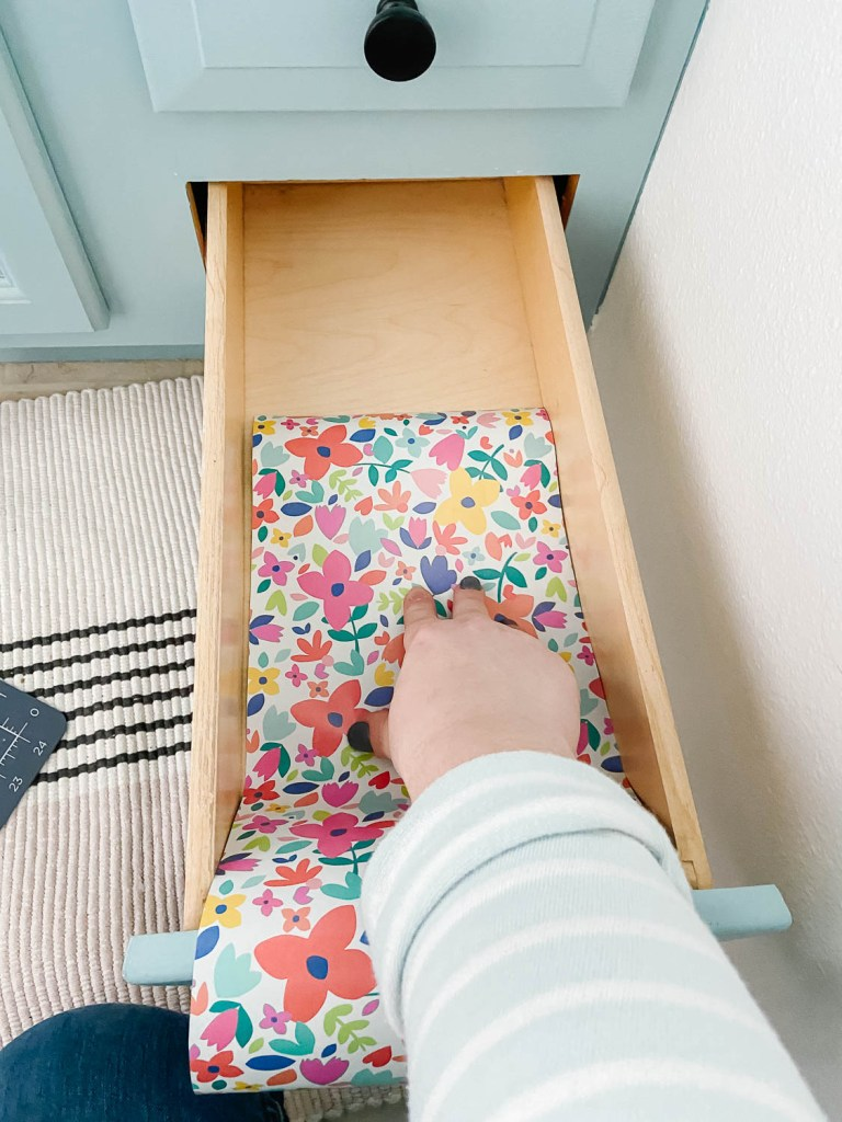 woman putting a colorful drawer liner in bathroom drawer