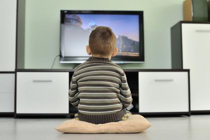 Kleinkind sitzt vor dem Fernseher und schaut einen Film