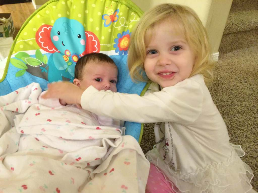 smiling toddler giving her baby sister a hug