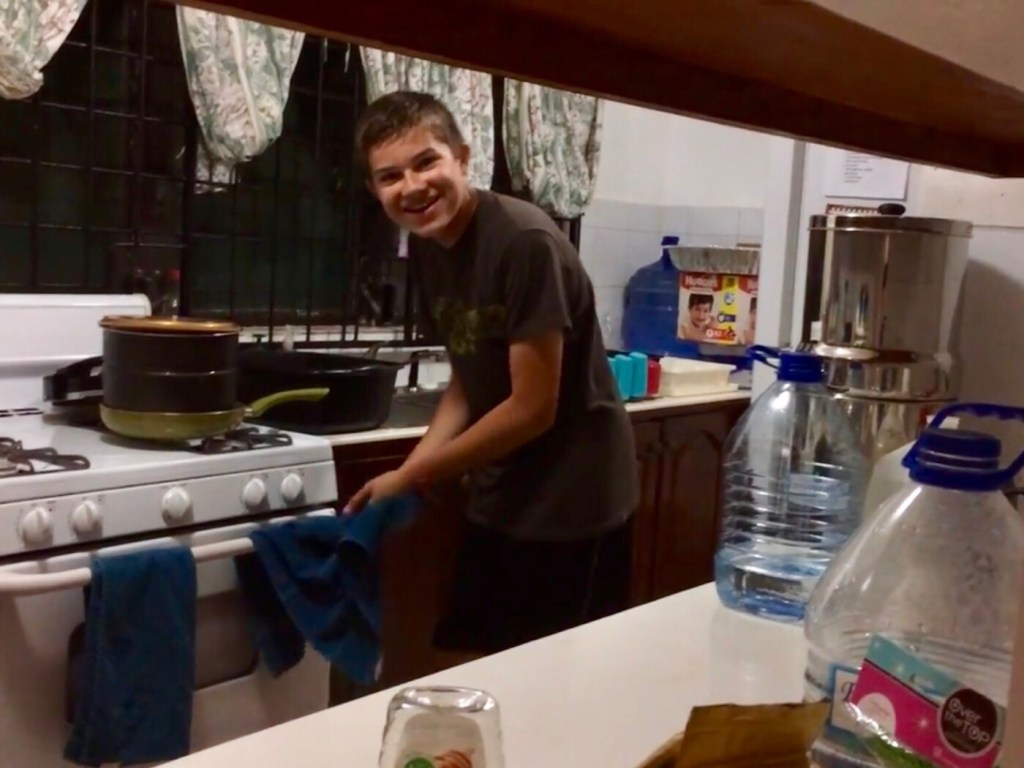 smiling boy washing dishes by hand
