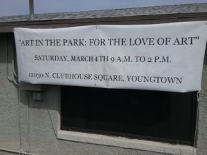 banner hanging at youngtown az city hall with dates and times of the youngtown art in the park show 201