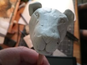 a close up of a lions head sculpted out of grey clay