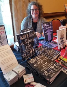 Laura packer poses behind a table with copies of her Audience to Zeal book.