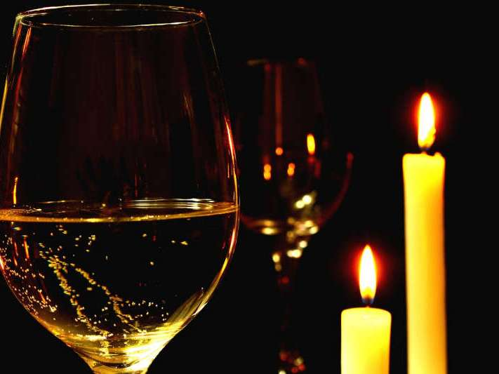 Romantic dinner with wine and candlelight.