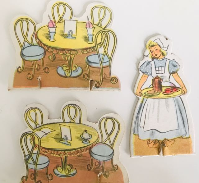 Three cardboard cut-outs: two of café tables and chairs, one of waitress carrying tray of tea or coffee and 2 cups.