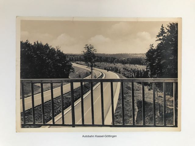 photo of a page from Martin Parr's 'Boring Postcard, German edition. Black and white. showing view from bridge across motorway. Motorway is empty.