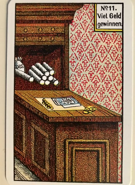 Kipper Card No 11: Winning lots of money: A desk and cupboard full of coins and some banknotes.