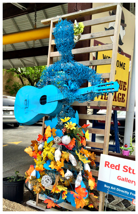 Wire art blue man playing a guitar in Kensington, Maryland