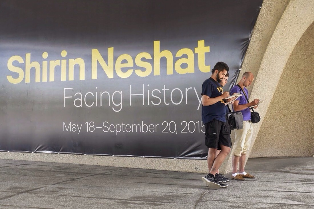 three men facing away from a poster advertising the Facing history at the hirshhorn museum in washington dc