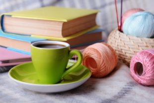 Cup of coffee and yarn for knitting on plaid with books close-up